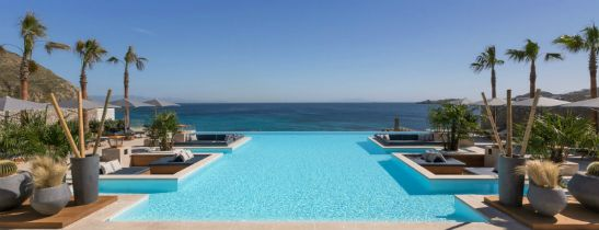 Oasis Pool by day overlooking the bay of Ornos and the private beach of Santa Marina Resort in Mykonos